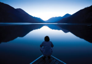 Mindful person looking over calm water
